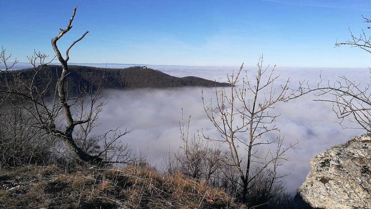 Das Bild zeigt die Aussicht von einem Berg in ein Tal, das gefüllt mit Wochen ist. Der Himmel darüber ist strahlend blau.