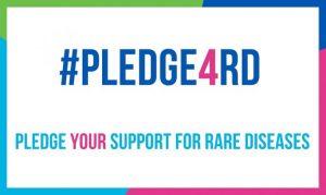 Schild in bunter Schrift. Das Bild zeigt den Hashtag pledge 4 RD und darunter den Schriftzug Pledge your support for rare diseases