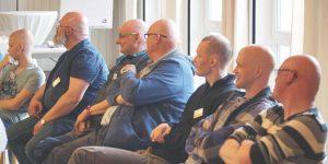 Zu sehen sind ed-Männer nebeneinander sitzend während einem Vortrag