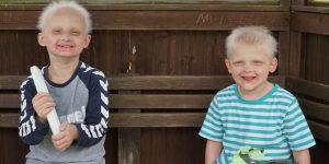 Zu sehen sind zwei ed-Kinder auf einer Bank sitzend