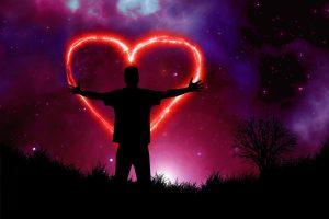Violetter Abendhimmel mit rotem stilisiertem Herz und einer Person die man aber nur als Schatten sieht
