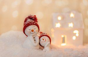 Zwei Schneemannfiguren mit roten Mützen. Die linke lächelt und hat geschlossene Augen.Die rechte ist etwas kleiner und schmachtet die linke an und lächelt.